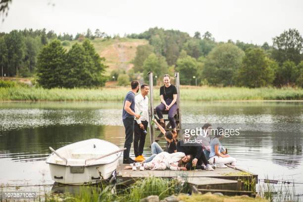 happy friends enjoying on jetty over lake during weekend getaway - moored stock pictures, royalty-free photos & images