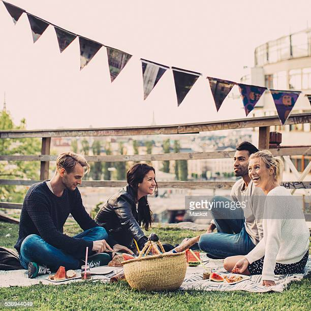 Happy friends enjoying picnic on roof garden