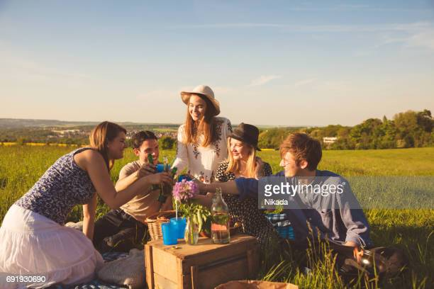 Gelukkig vrienden genieten van picnic met drankjes zittend op veld tegen hemel roosteren