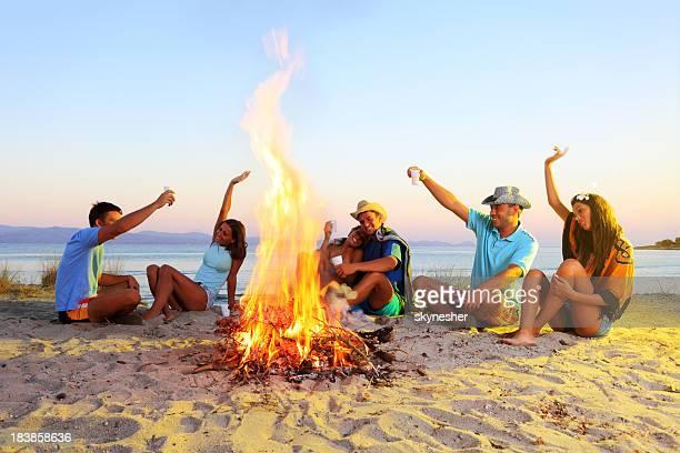 Heureux amis, assis à côté d'un feu de camp.