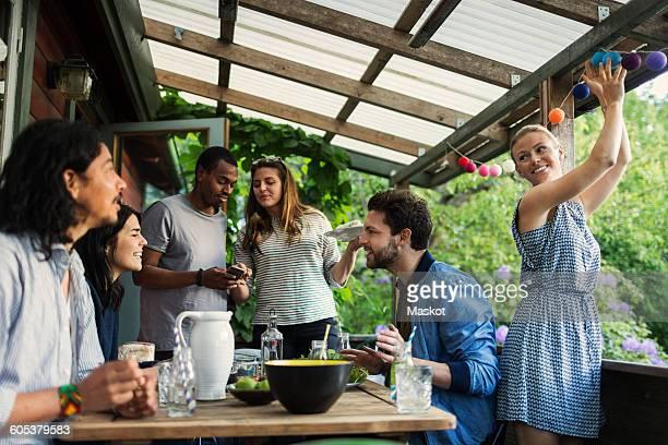 Happy friends enjoying summer party in log cabin