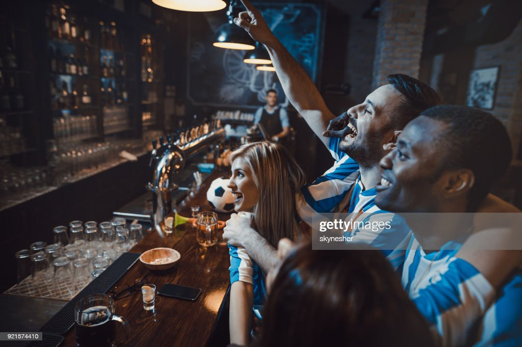 Happy friends enjoying while cheering for their soccer team in a bar. : Stock Photo
