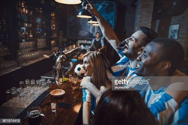 happy friends enjoying while cheering for their soccer team in a bar. - scoring a goal stock pictures, royalty-free photos & images