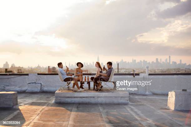 happy friends enjoying while having beer at building terrace during sunset - four people stock-fotos und bilder