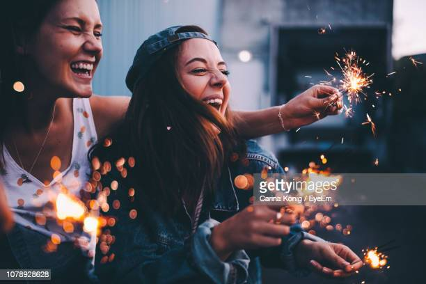happy friends enjoying while holding sparklers - fireworks stock pictures, royalty-free photos & images