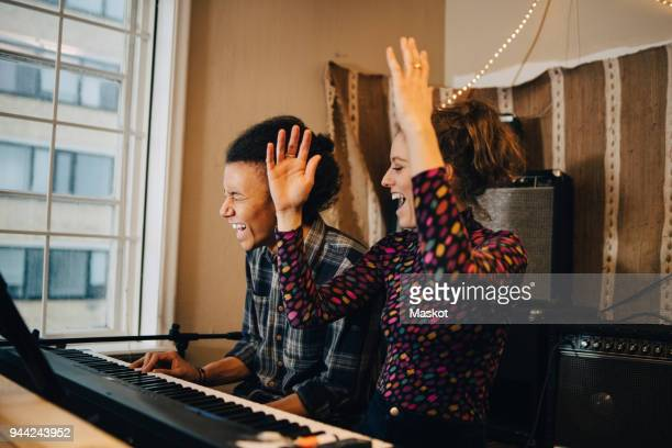 happy friends enjoying while playing piano and practicing at recording studio - rehearsal stock pictures, royalty-free photos & images