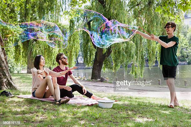 Happy friends enjoying with large bubble at park