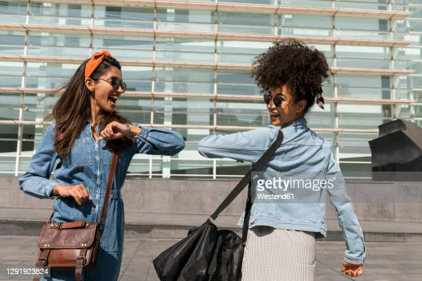 happy friends greeting with elbow bumps while standing on rooftop - crossbody bag stock pictures, royalty-free photos & images