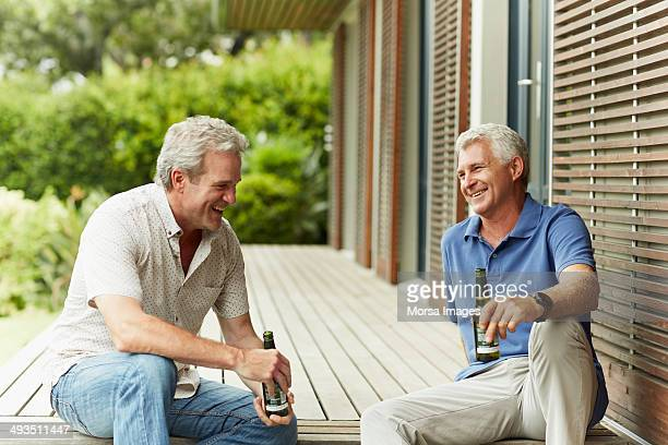 Happy friends having beer at yard