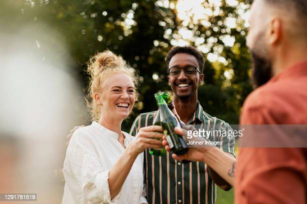 happy friends having beer in garden - three people stock pictures, royalty-free photos & images