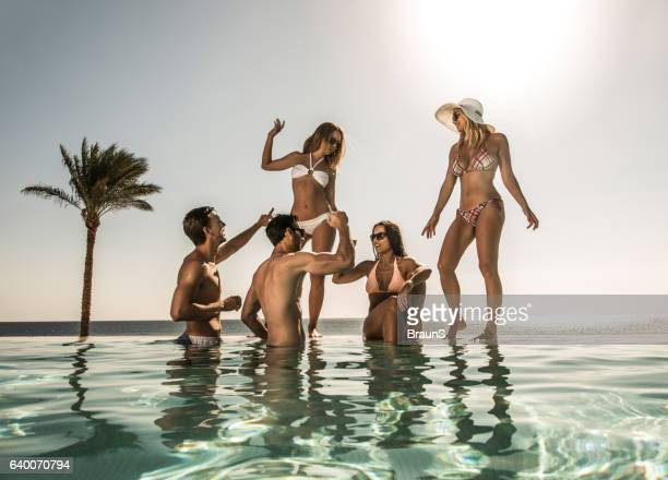 happy friends having fun at the infinity pool. - pool party stock pictures, royalty-free photos & images