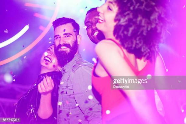 Happy friends having fun in night club with canon ball throwing confetti - Young people enjoying weekend nightlife with original laser lights color - Soft focus on bearded white man - Warm filter