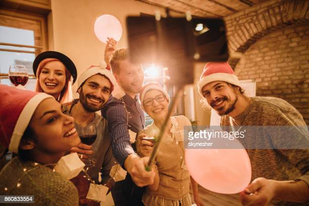 Happy friends having fun while taking a selfie at Christmas party.