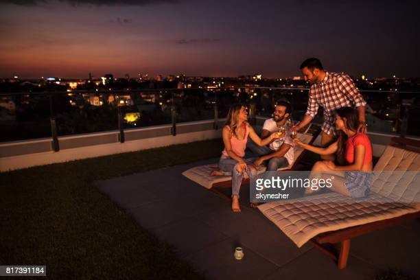 Amis heureux de s'amuser tout en grillage sur un balcon de l'appartement par nuit.