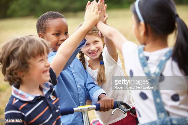 happy friends high-fiving at park - children only stock pictures, royalty-free photos & images
