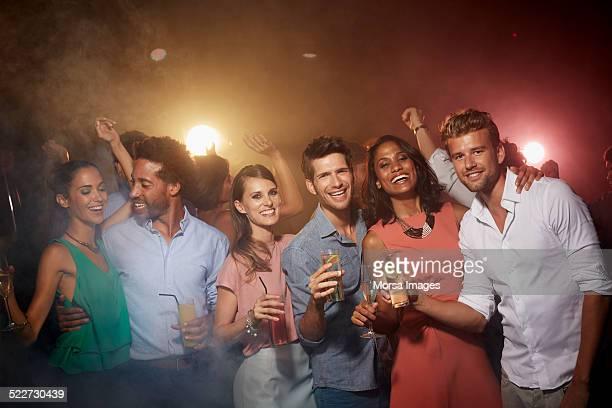 Happy friends holding drinks in nightclub