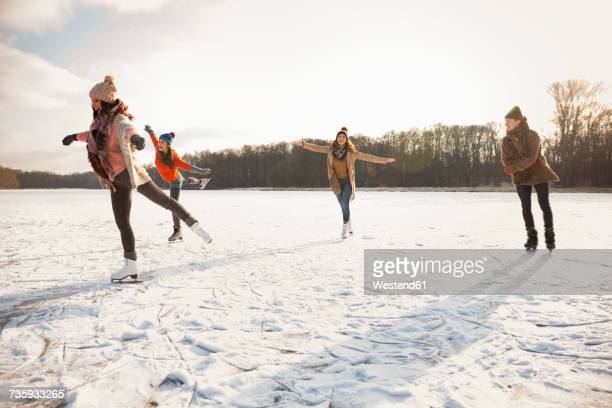 happy friends ice skating on frozen lake - ice skate stock pictures, royalty-free photos & images