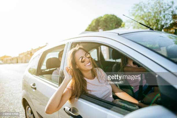 Happy friends in car seen from outside