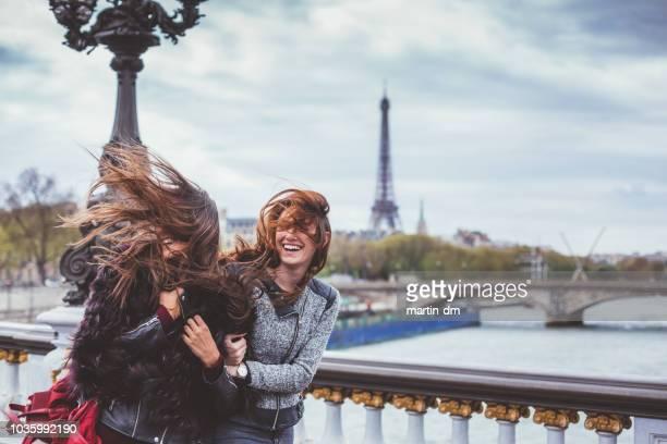 glückliche freunde in paris mit zerzausten haaren an windigen tag - paris stock-fotos und bilder