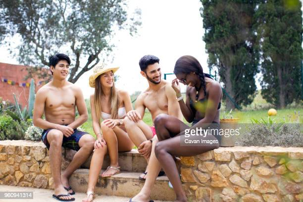 Happy friends in swimwear sitting on retaining wall at yard