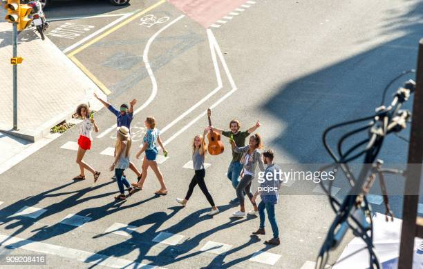 Happy Friends In The City. Top view of eight young adults crossing the street in the sun, looking at the camera, shot in Barcelona, Spain.