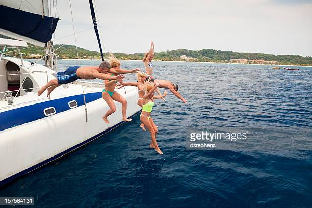 happy friends jumping off catamaran into caribbean sea - catamaran stock photos and pictures