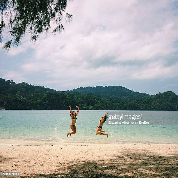 happy friends jumping on beach - malaysia beautiful girl stock photos and pictures