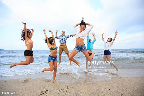 Happy friends jumping on sand at beach