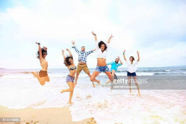 Happy friends jumping over the water