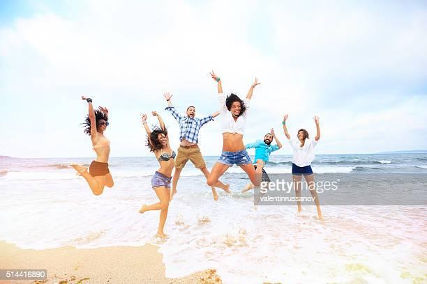Felices amigos saltar sobre el agua