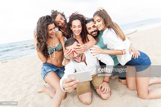 Happy friends kneeling on sand and making selfe