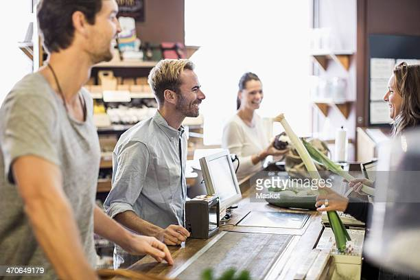 Happy friends looking at cashier at checkout counter in grocery store