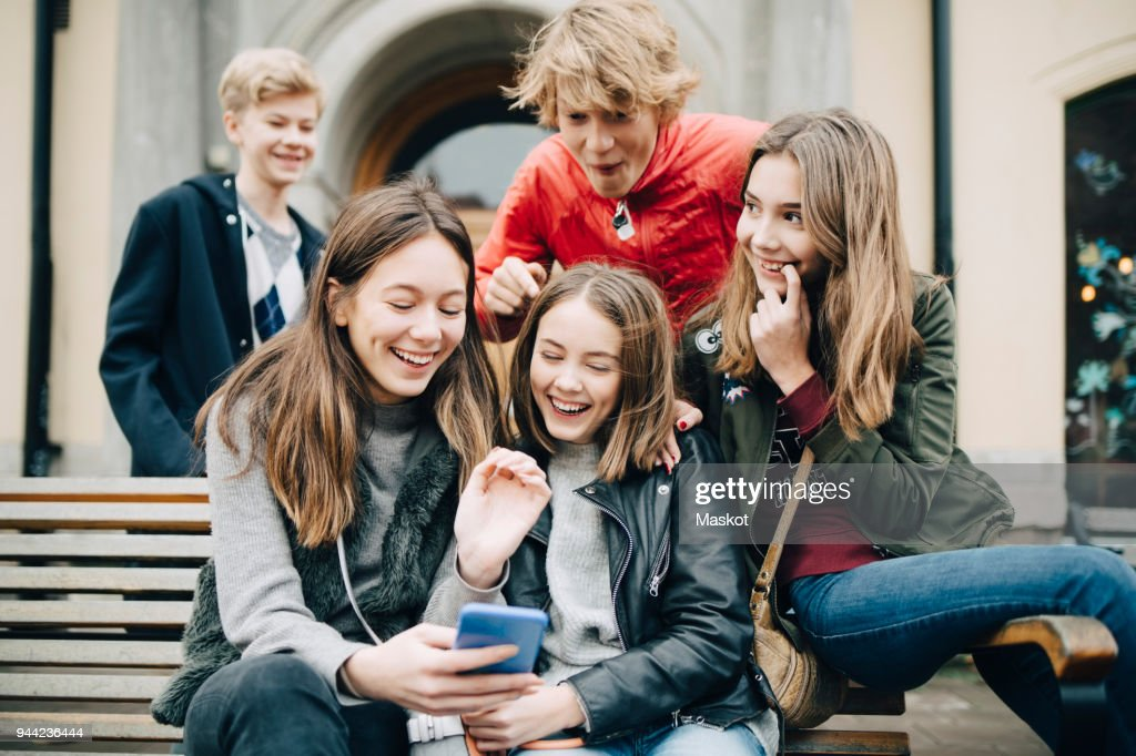 Happy friends looking at smart phone while sitting on bench at city : Stock-Foto