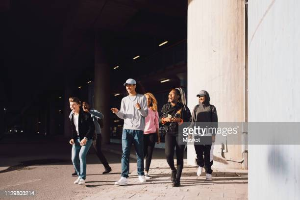 happy friends looking away while walking on street under overpass in city during sunny day - carefree ストックフォトと画像