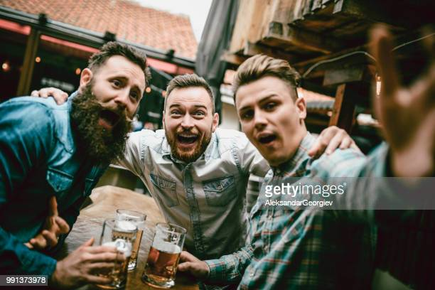 happy friends making faces while drinking beer in bar - binge drinking stock photos and pictures