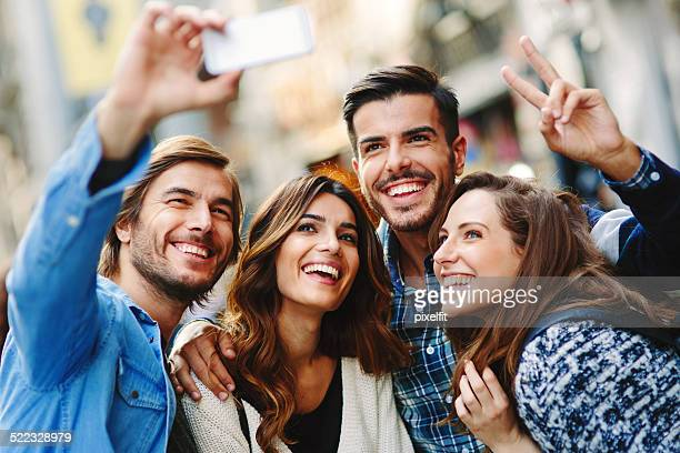 Happy friends making selfie in the city