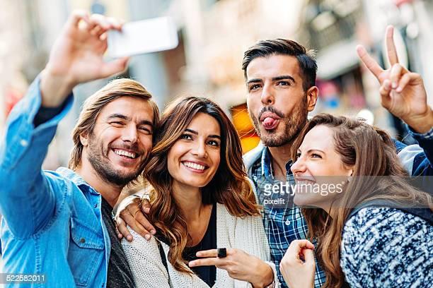 Happy friends making selfie in the city