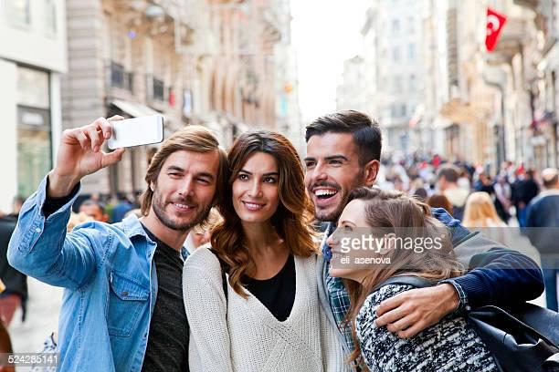 Happy friends making selfie in the city.