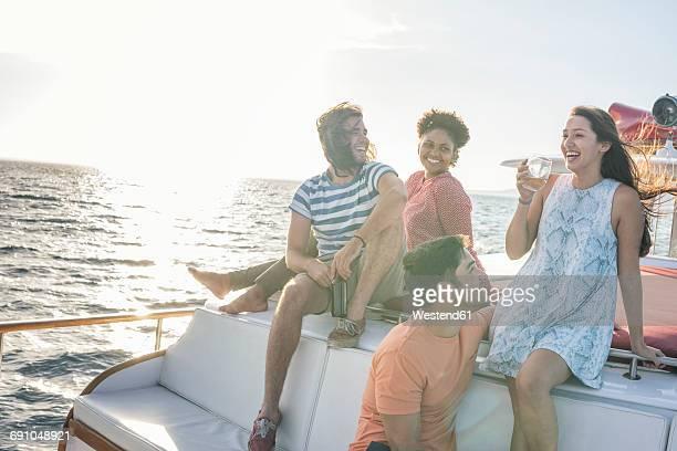 Happy friends on a boat trip having a drink