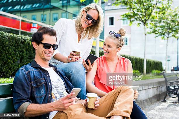 Happy friends on bench looking at smartphones