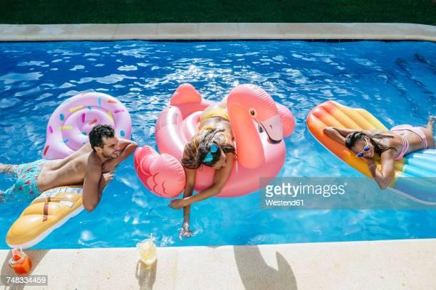happy friends on floats in swimming pool - ao lado de piscina - fotografias e filmes do acervo