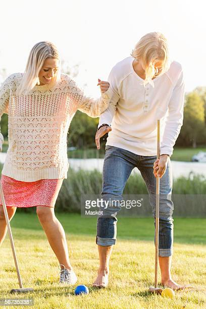 Happy friends playing croquet on field