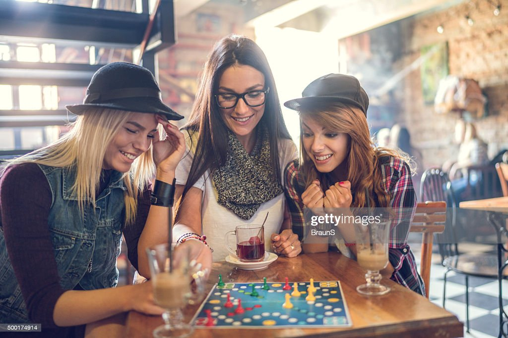 Happy friends playing cross and section game in a cafe. : Stock Photo