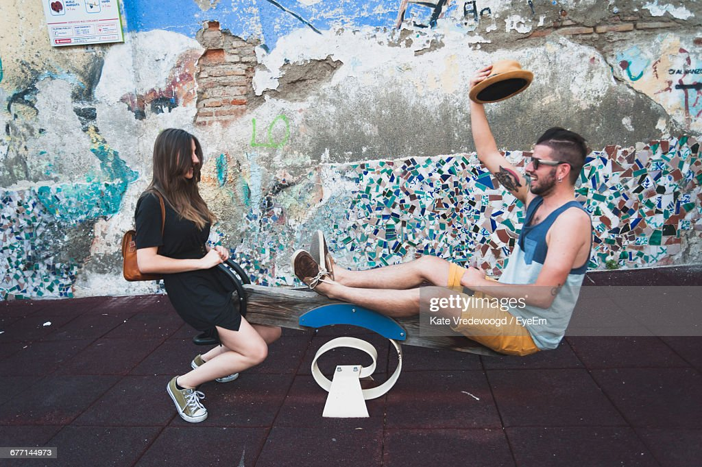 Happy Friends Playing Seesaw Against Damaged Wall : Stock Photo