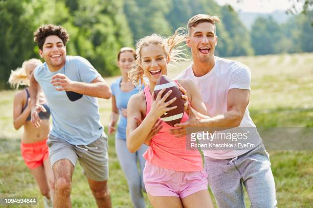 happy friends playing with ball on field at park - moving after stock pictures, royalty-free photos & images