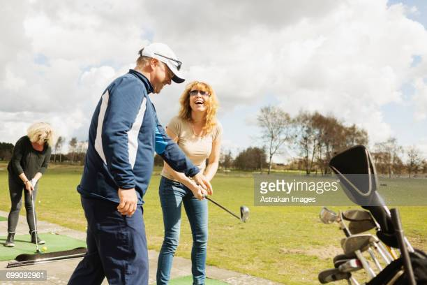 happy friends practicing golf at driving range on sunny day - driving range stock photos and pictures
