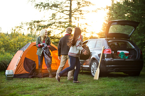 Happy friends preparing tent by car on field in forest - gettyimageskorea