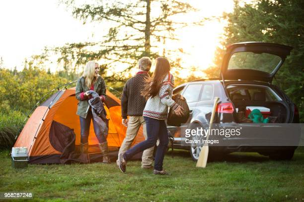 happy friends preparing tent by car on field in forest - white boot stock pictures, royalty-free photos & images