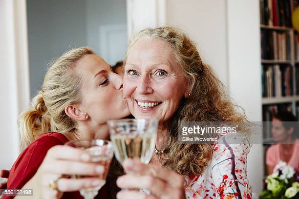 happy friends raise a glas of sparkling wine at a party - brindisi bicchieri foto e immagini stock
