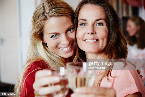 happy friends raise a glas of sparkling wine at a party